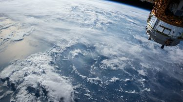 Looking down at the Earth with a satellite in the foreground